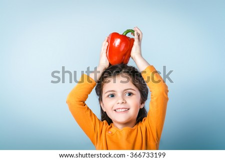 Portrait of cute little smiling girl. Girl wearing orange blouse and having fun while holding fresh red paprika on head. Girl standing against grey background - stock photo