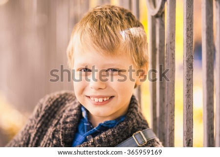 Portrait of cute little smiling kid on sunny beautiful autumn day. Smiling face of blond boy looking at camera. Horizontal color image of beautiful joyful child playing outside.
