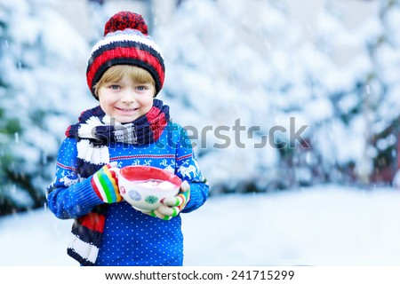 Portrait of cute little toddler boy in winter clothes with falling snow. Kid enjoying and catching snowflakes, outdoors on cold day. - stock photo