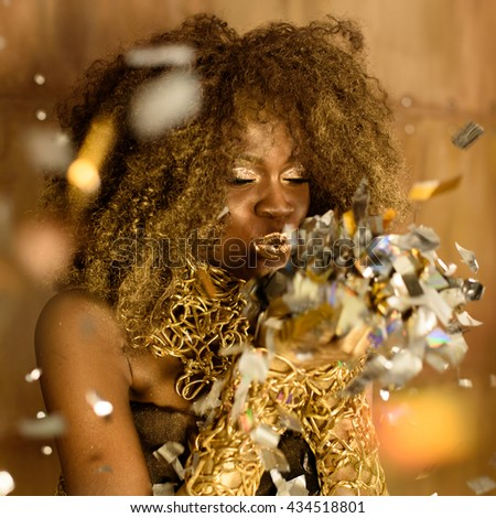 Portrait of cute lovely young woman blowing on small sparkling stars over gold background - stock photo
