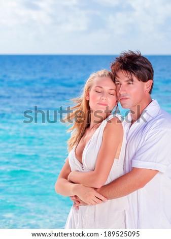 Portrait of cute loving couple hugging on the beach, enjoying summer vacation, romantic date on seashore, love concept - stock photo