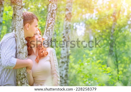 Portrait of cute loving couple in the park enjoying warm sunny day, spending time in birch grove, romantic date, love and happiness concept  - stock photo