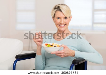 portrait of cute mature woman in wheelchair eating fruit salad - stock photo
