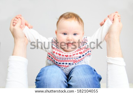 portrait of cute newborn baby girl on parent lap - stock photo