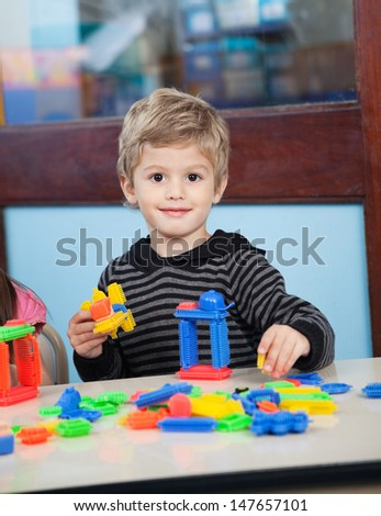 Portrait of cute preschool boy playing with blocks in kindergarten - stock photo