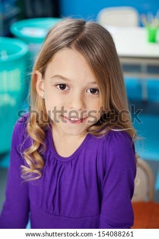 Portrait of cute preschool girl smiling in classroom - stock photo