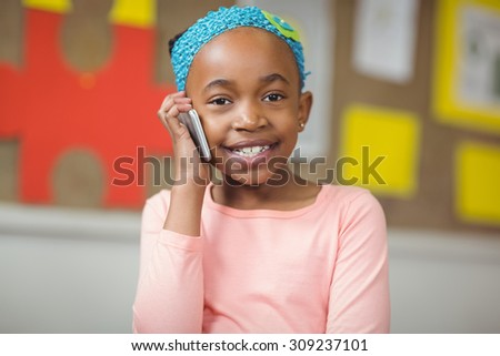 Portrait of cute pupil phoning with smartphone in a classroom in school - stock photo