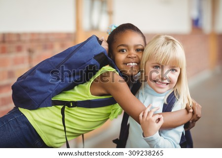 Portrait of cute pupils embracing at corridor in school