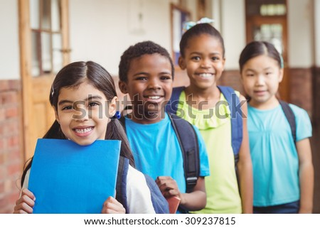 Portrait of cute pupils standing in a row at corridor in school - stock photo