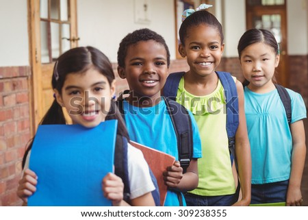 Portrait of cute pupils standing in a row at corridor in school