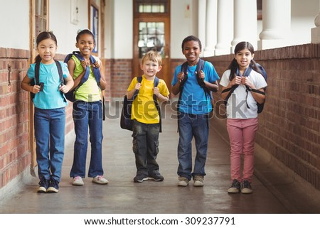 Portrait of cute pupils with schoolbags standing at corridor in school - stock photo