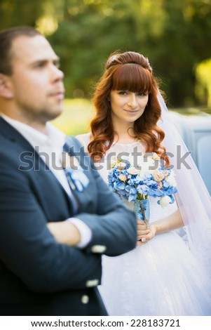 Portrait of cute redhead bride holding bouquet and looking at groom - stock photo