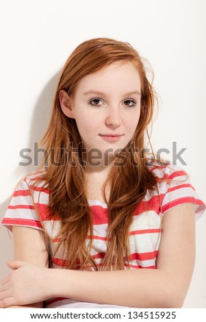 portrait of cute redheaded girl, background wall - stock photo