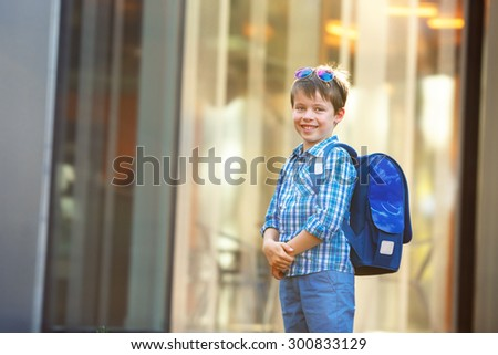 Portrait of cute school boy with backpack outdoors  - stock photo
