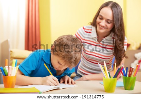 Portrait of cute schoolboy and his mother making schoolwork at home - stock photo