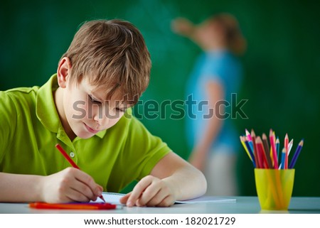Portrait of cute schoolboy drawing with colorful pencils - stock photo