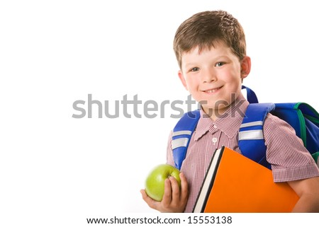 Portrait of cute schoolboy holding green apple and book looking at camera over white background - stock photo