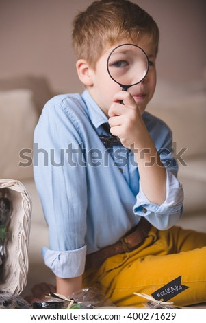 Portrait of cute schoolboy kid in blue shirt sitting on the sofa and looking through a magnifier. Child watching through magnifying glass. Indoors. - stock photo