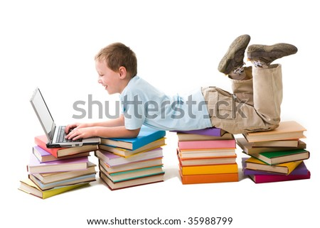 Portrait of cute schoolboy lying on top of book stacks and typing on laptop keyboard