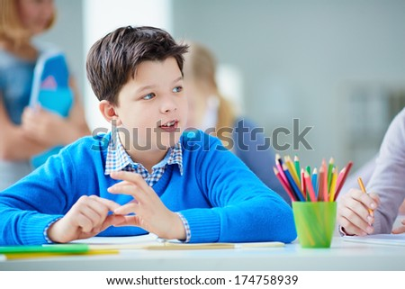 Portrait of cute schoolboy sitting at lesson on background of his classmates - stock photo