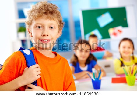 Portrait of cute schoolboy with backpack looking at camera with his classmates on background - stock photo