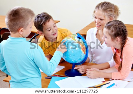 Portrait of cute schoolchildren and teacher looking at globe at geography lesson - stock photo