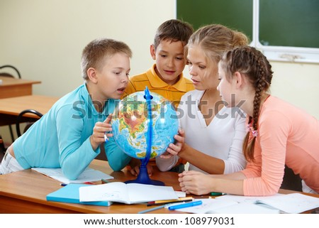 Portrait of cute schoolchildren and teacher looking at globe in classroom - stock photo