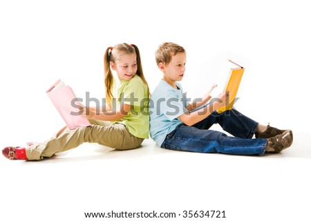 Portrait of cute schoolchildren holding open books and reading them - stock photo