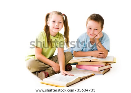 Portrait of cute schoolchildren looking at camera during reading books - stock photo