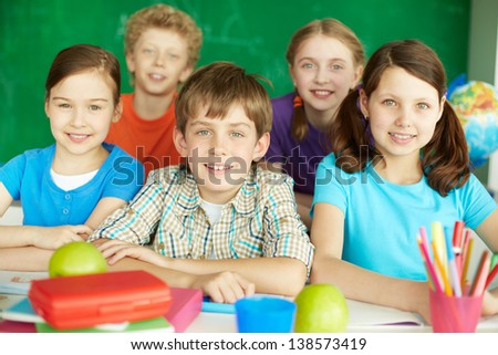 Portrait of cute schoolchildren looking at camera in classroom - stock photo
