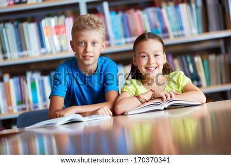 Portrait of cute schoolchildren looking at camera while sitting in library - stock photo