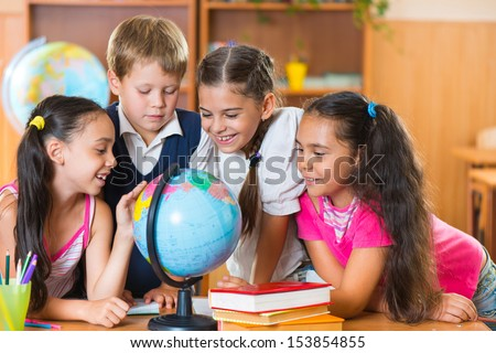 Portrait of cute schoolchildren looking at globe in classroom - stock photo