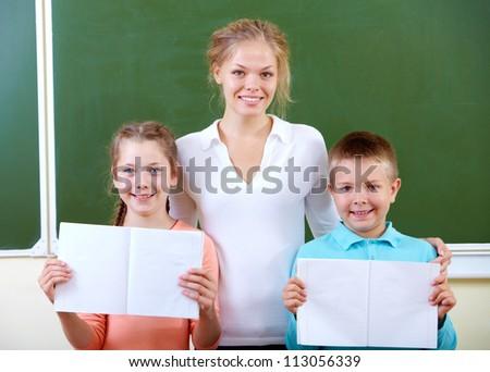 Portrait of cute schoolchildren showing their copybooks with teacher near by - stock photo