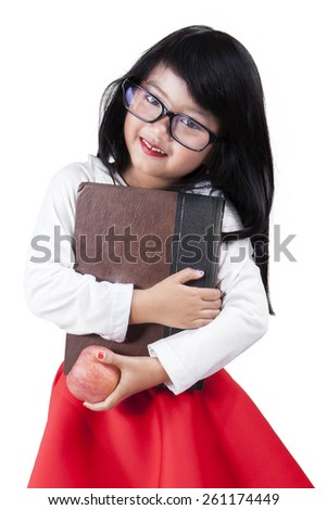 Portrait of cute schoolgirl holding a book and apple while smiling at the camera, isolated on white - stock photo