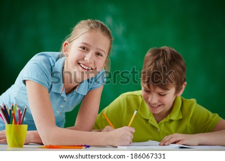 Portrait of cute schoolgirl looking at camera while drawing at lesson with classmate near by - stock photo