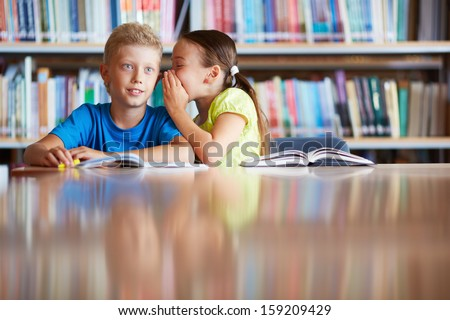 Portrait of cute schoolgirl whispering something to her classmate in library - stock photo