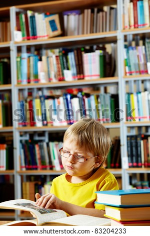 Portrait of cute schoolkid reading book in the library