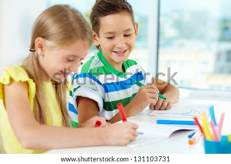 Portrait of cute schoolkids drawing at lesson - stock photo