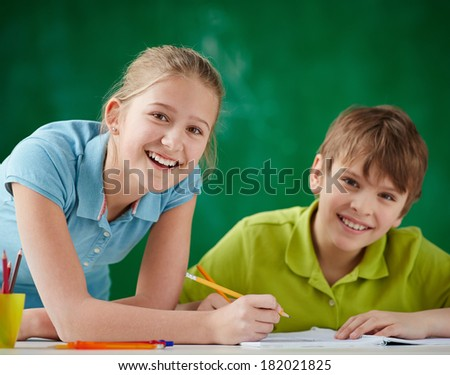 Portrait of cute schoolkids looking at camera while drawing at lesson - stock photo