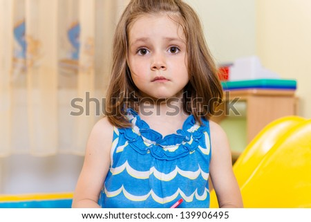 Portrait of cute serious little girl standing in playroom - stock photo
