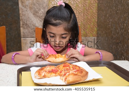 Portrait of cute sleepy little girl / kid/ child eating tasty pizza in restaurant Kerala, India, Asia. Tired young / small Indian girl sitting by dinner table sleeping holding pizza with both hands. - stock photo