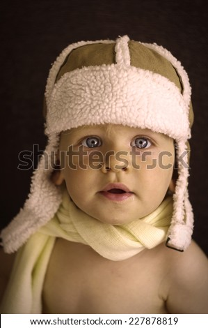 Portrait of cute smiling baby boy in winter pilot hat and wrap. Use it for a child, winter or parenthood concept. Vintage portrait. - stock photo