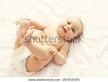 Portrait of cute smiling baby lying on the bed at home, top view - stock photo