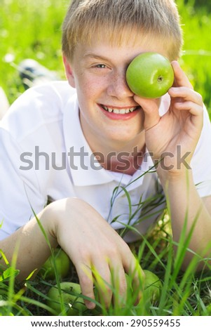 Portrait of cute smiling boy with freckles on his face is holding two green apples