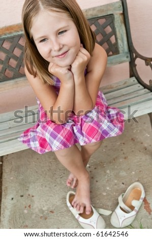 Portrait of cute smiling child sitting on bench - wall in background - stock photo
