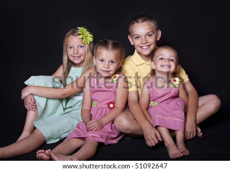 Portrait of cute, smiling children on a black background. - stock photo
