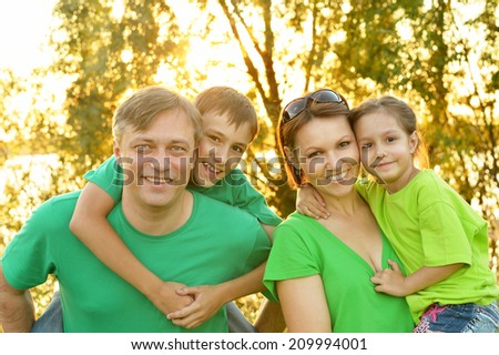 Portrait of cute smiling friendly family outdoor - stock photo
