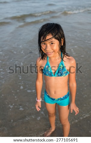 Portrait of cute smiling girl in blue swimsuit against the beach. - stock photo