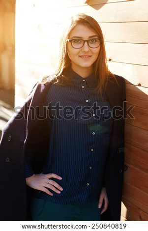 Portrait of cute smiling girl looking at you standing outdoors at sunny evening - stock photo