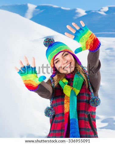 Portrait of cute smiling girl waving hands, wearing stylish colorful outfit, spending active winter holidays in the snowy mountains